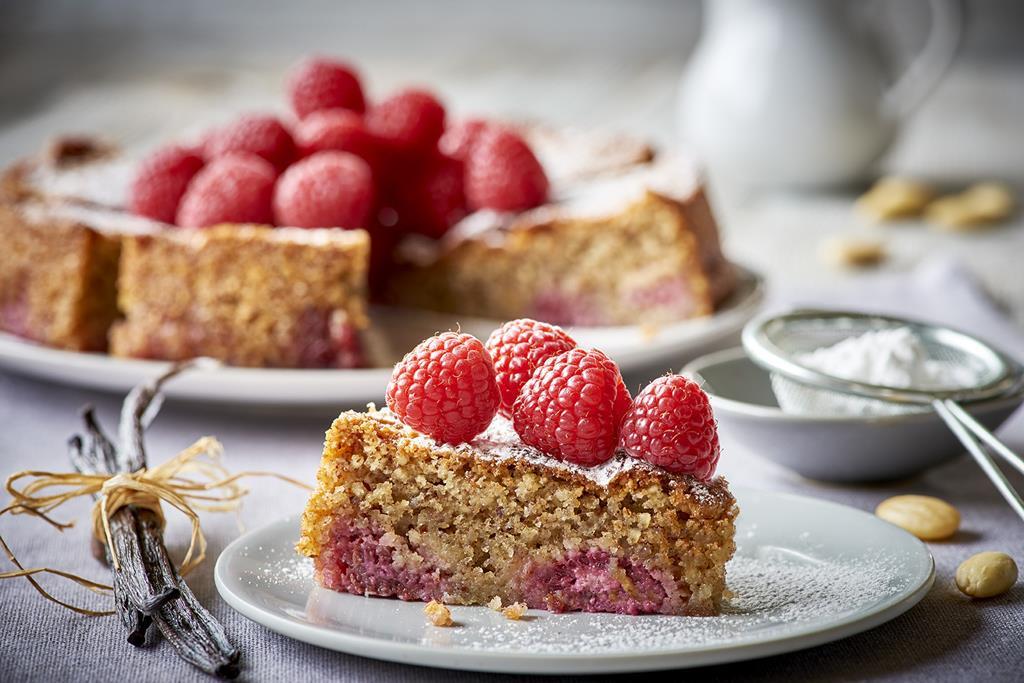 Ciasto migdałowe z malinami oprószone cukrem pudrem na talerzyku - Wszystkiego Słodkiego