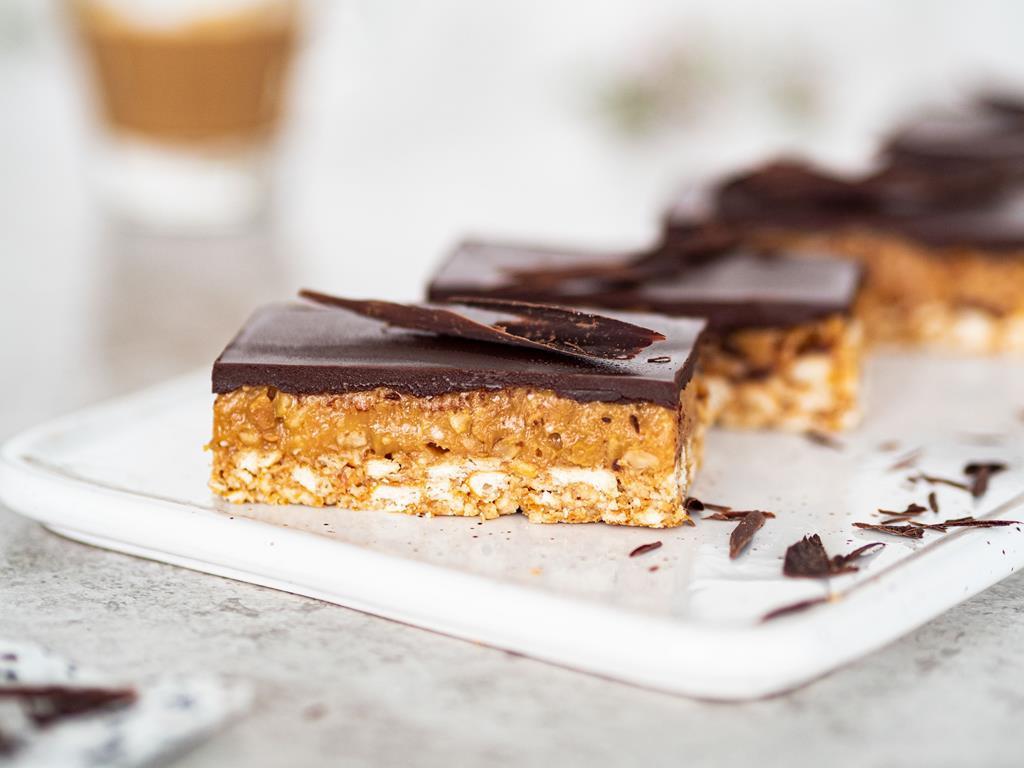 Ciasto Milionera z czekoladową polewą bez pieczenia na talerzu